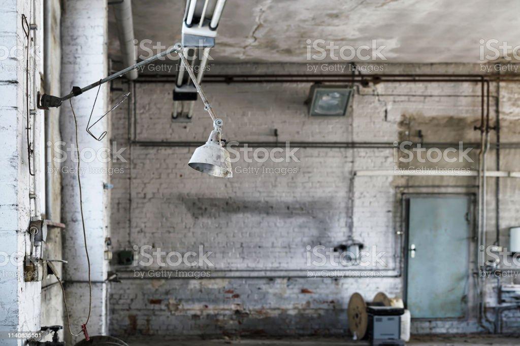 Lampe am Arbeitsplatz in einer verlassenen Werkstatt – Foto