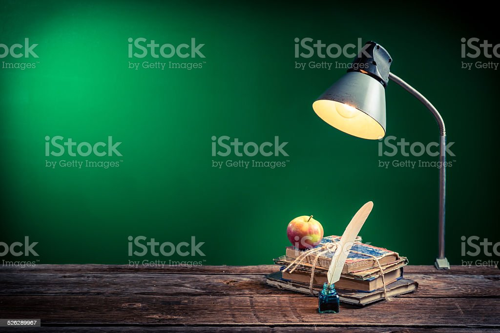 Lamp, books and apple in the classroom on blackboard background stock photo