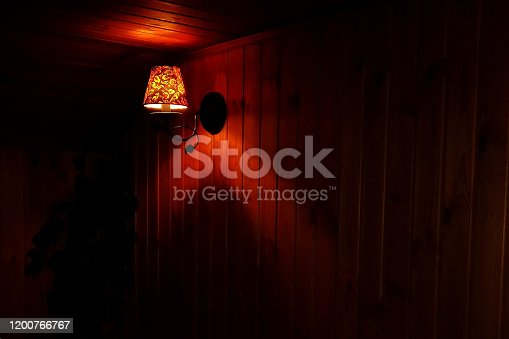 Lamp in a dark wooden room with yellow light