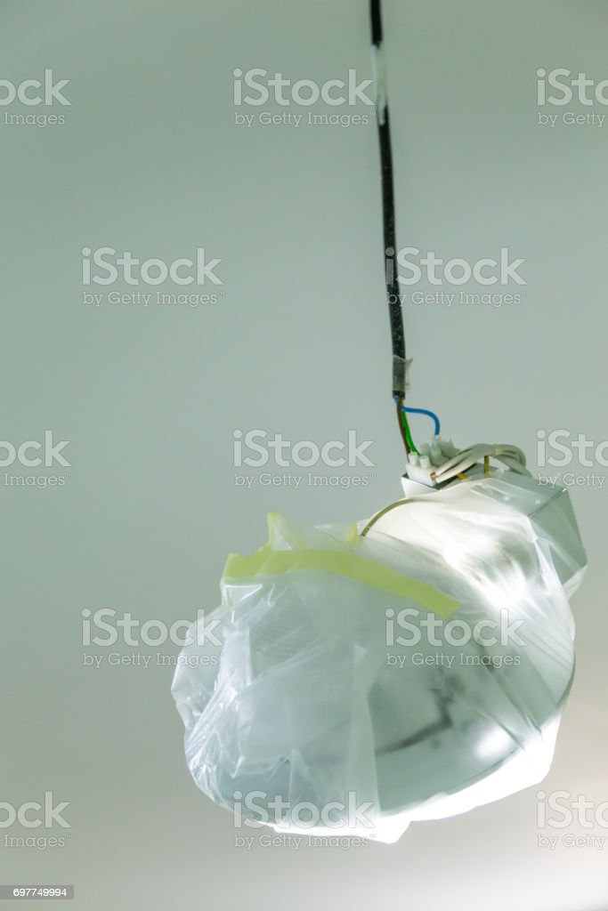 lamp in protection tape is preparation for painting interior at home stock photo