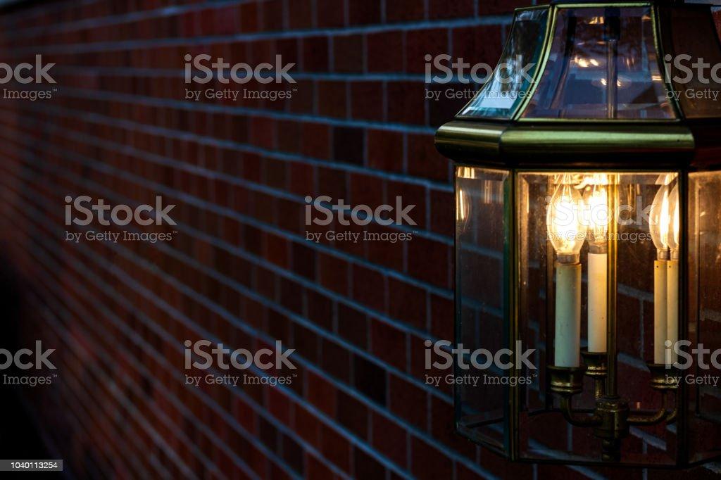 Lamp mounted on a brick wall illuminating golden light stock photo