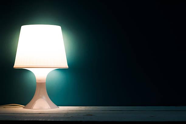 lampe licht in einem dunklen hintergrund - nachttischleuchte stock-fotos und bilder