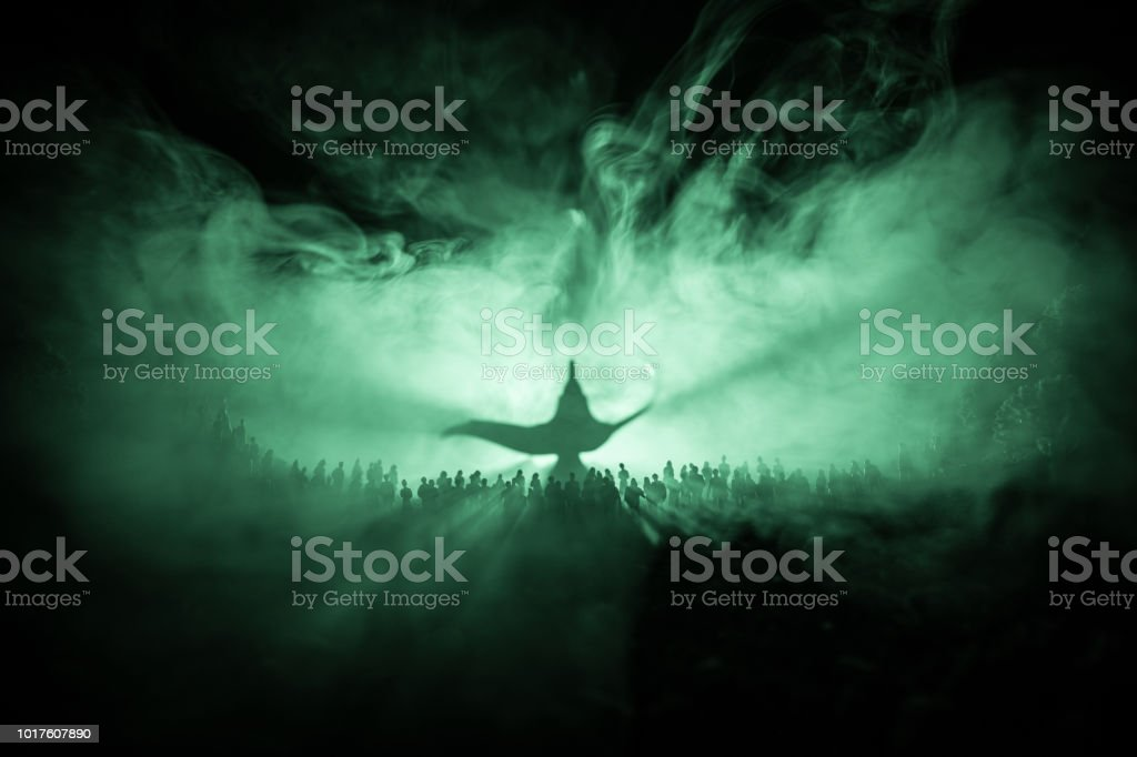 Lamp of wishes. Silhouette of a large crowd of people standing against a big lamp of wishes with toned light beams on foggy background. Dark night table decoration. стоковое фото