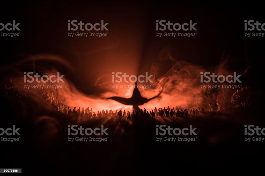 Lamp of wishes. Silhouette of a large crowd of people standing against a big lamp of wishes with toned light beams on foggy background. Dark night table decoration. stock photo