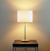 Lamp on table with painted wall background. Home energy utilities, electric lighting fixtures and contemporary, modern interior decor elements.