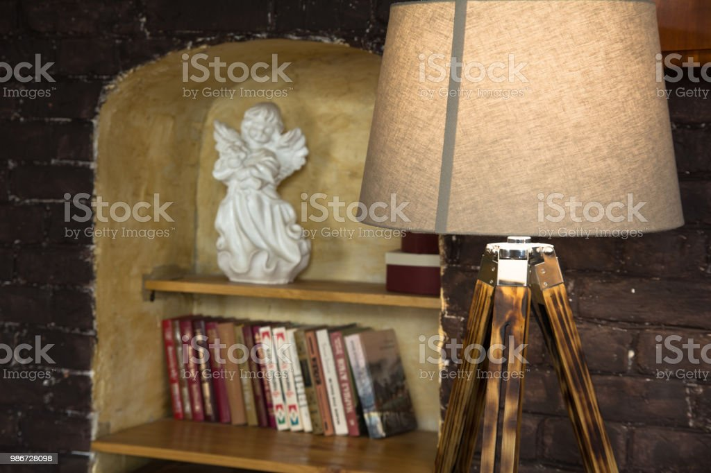 Lamp On Wooden Legs And Bookshelf With Porcelain Angel In A Niche Royalty Free Stock