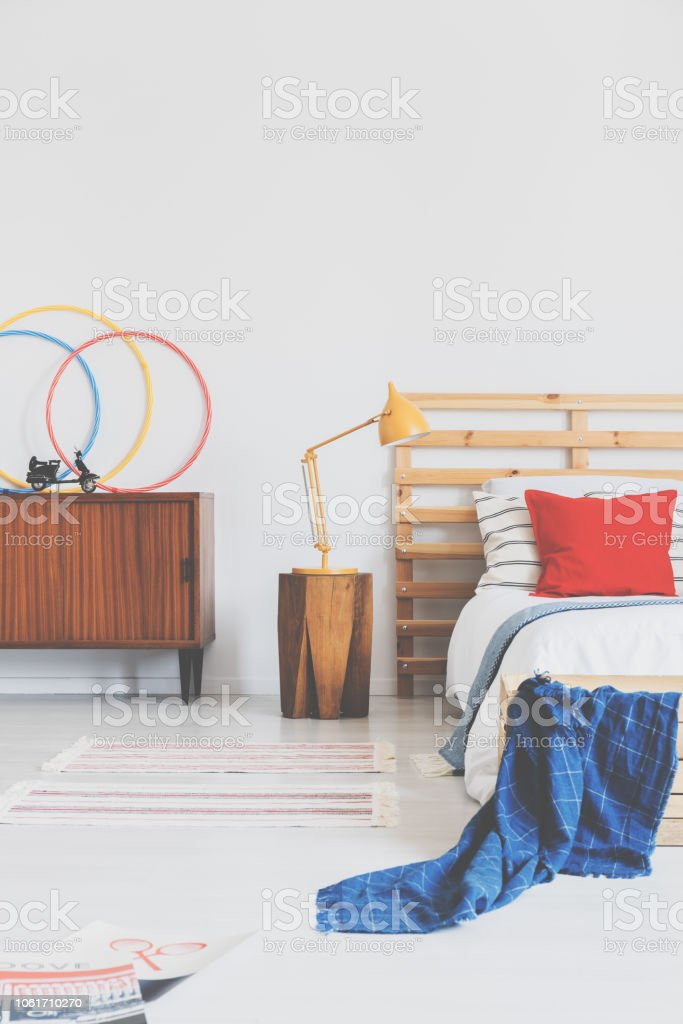Lamp on wooden stool next to bed with red cushion and blue blanket in bedroom interior. Real photo stock photo
