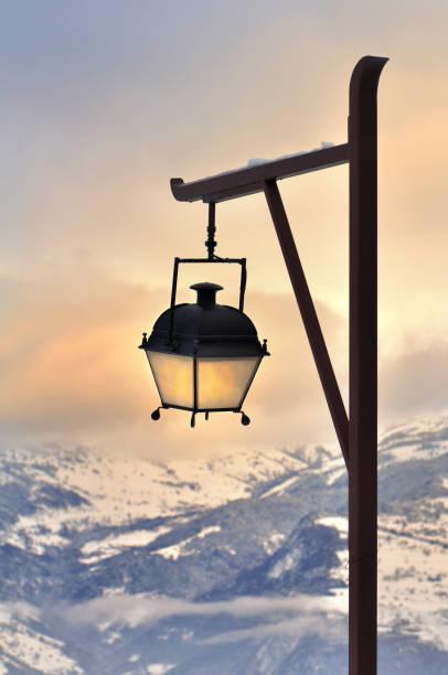 poste de la lámpara frente a una hermosa puesta de sol en la montaña nevada - foto de stock