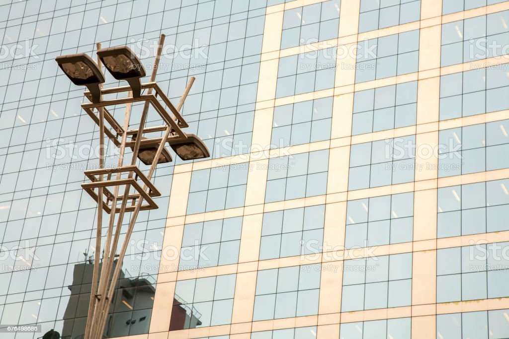 Lamp post in front of a Glass and concrete facade on a modern corporate skycraper building stock photo