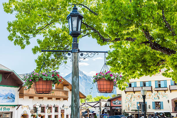 lamp post with hanging flower pots - leavenworth washington stock photos and pictures