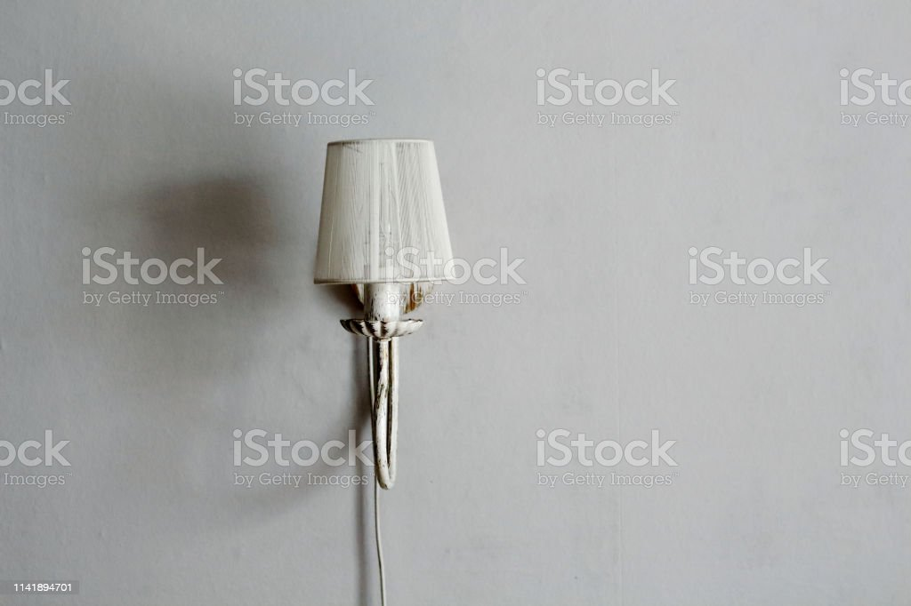 Lamp sconces on a gray wall with shadows in the interior design room...