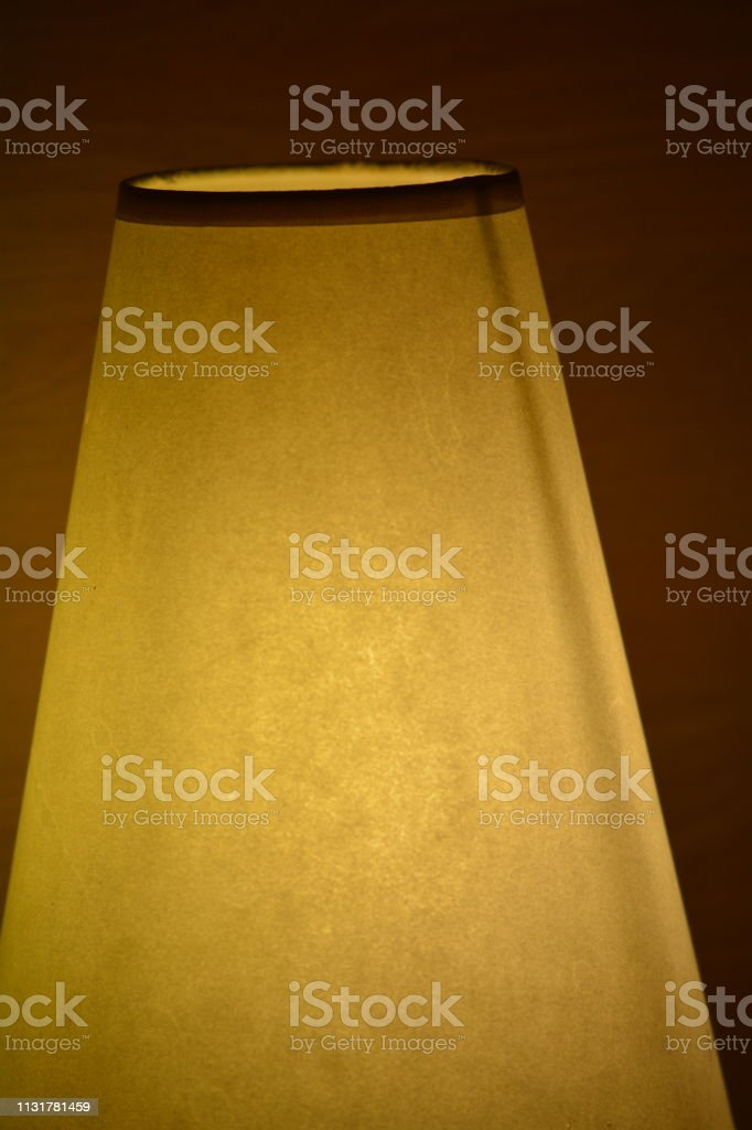 An extreme close-up of a cone shaped lamp shade illuminated and...