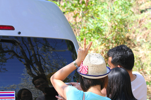 Lampang, Thailand February 28, 2015. Travel with friends on a hill. Before returning home, take a picture from a mobile camera through the mirror at the back of the van. With a woman wearing a hat standing up behind her raised two fingers.