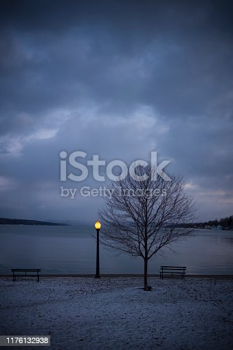 A lamppost illuminates at a lakeside park in Skaneateles, New York, USA, a small town in the Finger Lake Region at dusk in the winter.