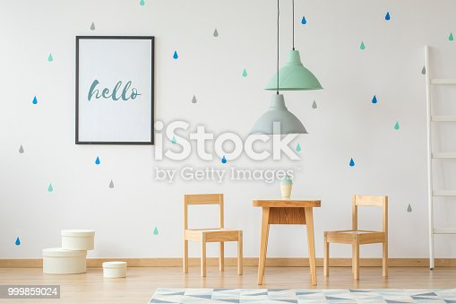 istock Lamps above wooden table and chairs in bright kid's room interior with poster on the wall. Real photo 999859024