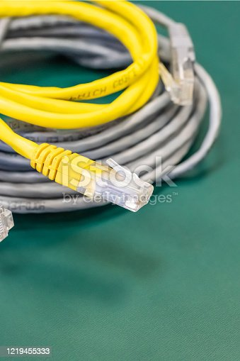 istock Lan cable with rJ45 connector, pair of coil wires yellow and gray 1219455333