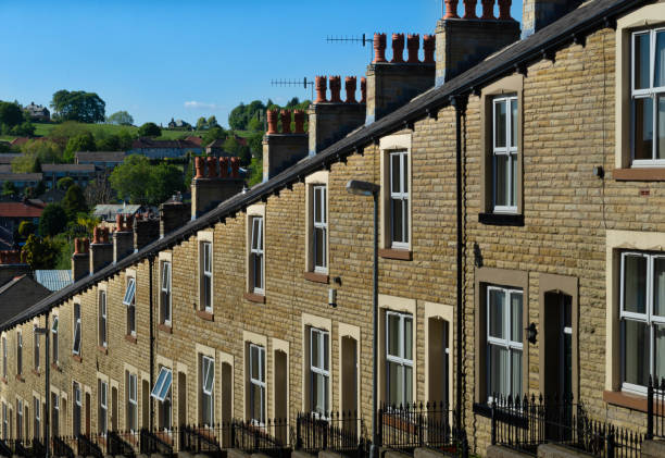Lancashire Stone built terraced housing A typical row of Lancashire town stone facade built and slate roof covered terraced houses. Red chimney stacks top the buildings with the hills visible in the distance northwest england stock pictures, royalty-free photos & images