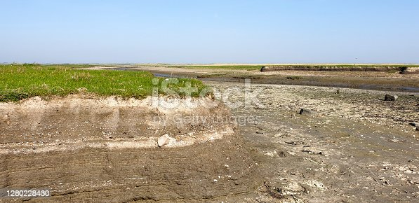 Ameland, the Netherlands - September 15, 2020: The creek in the salt marsh landscape on the Wadden island of Ameland is almost dry during low tide. The layers in the ground are now clearly visible.