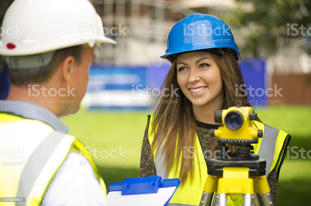 female land surveyor chatting to a colleague
