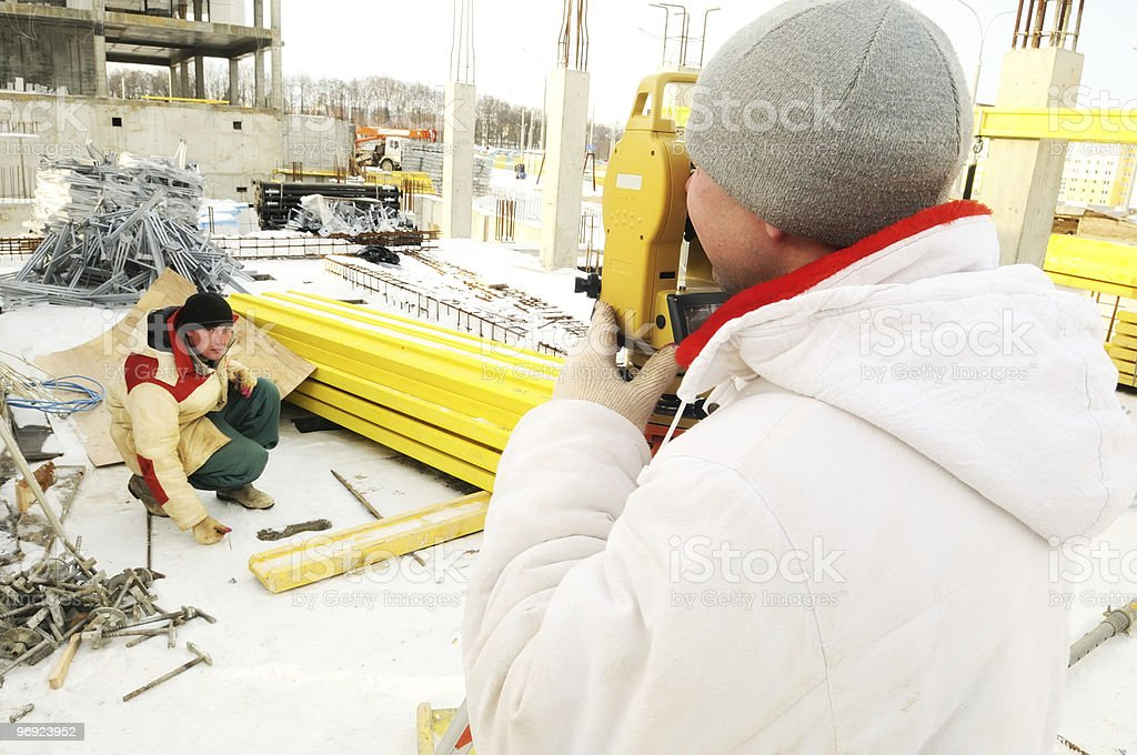 land surveyor workers using theodolite equipment at construction royalty-free stock photo