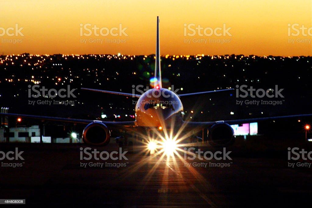 Aeronave pousou no pôr do sol com faróis no aeroporto foto royalty-free
