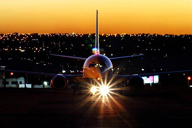 Aeronave pousou no pôr do sol com faróis no aeroporto - foto de acervo