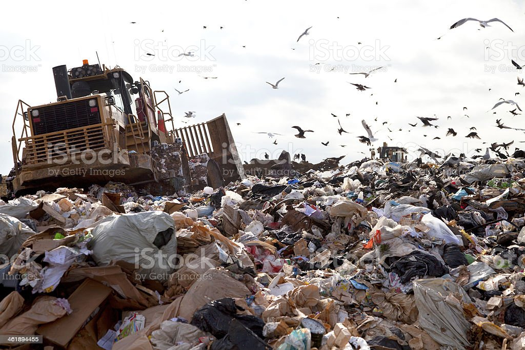 Landfill truck in trash stock photo