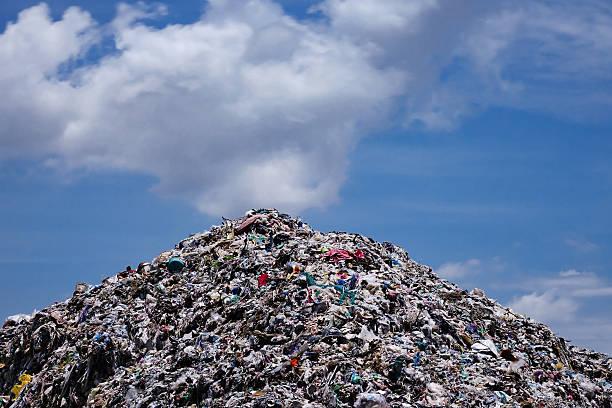 landfill with blue sky and cumulus clouds - détritus photos et images de collection