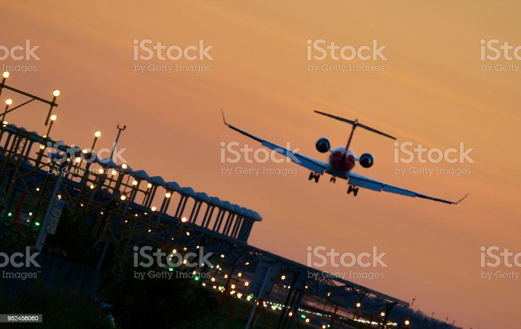 Landing airplane during sunset - Barcelona 'El Prat Aeroport' stock photo