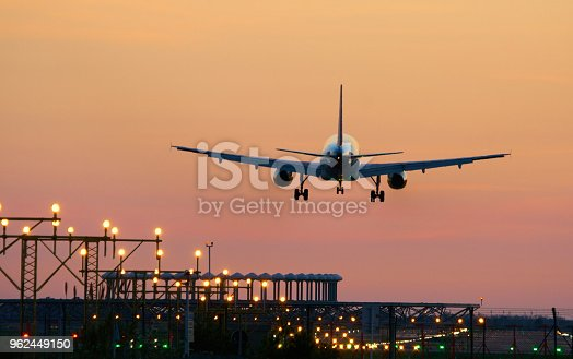 Airplane landing during sunset in Barcelona