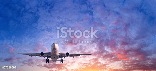 816320512 istock photo Landing airplane. Landscape with passenger airplane is flying in the blue sky with red, purple and orange clouds at sunset. Travel background. Passenger airliner. Commercial aircraft. Private jet 857236598