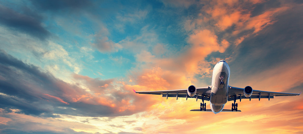 istock Landing airplane. Landscape with white passenger airplane is flying in the blue sky with multicolored clouds at sunset. Travel background. Passenger airliner. Business trip. Commercial aircraft 816320512