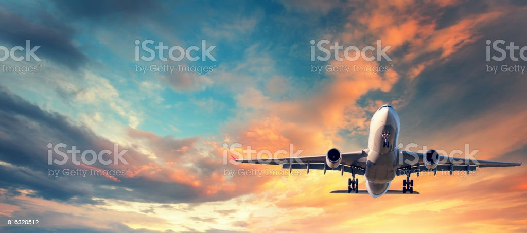 Landing airplane. Landscape with white passenger airplane is flying in the blue sky with multicolored clouds at sunset. Travel background. Passenger airliner. Business trip. Commercial aircraft - foto stock