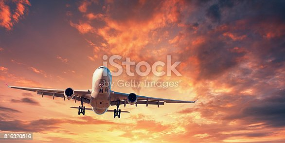 816320512 istock photo Landing airplane. Landscape with white passenger airplane is flying in the orange sky with clouds at colorful sunset. Travel background. Passenger airliner. Business trip. Commercial aircraft. Concept 816320516