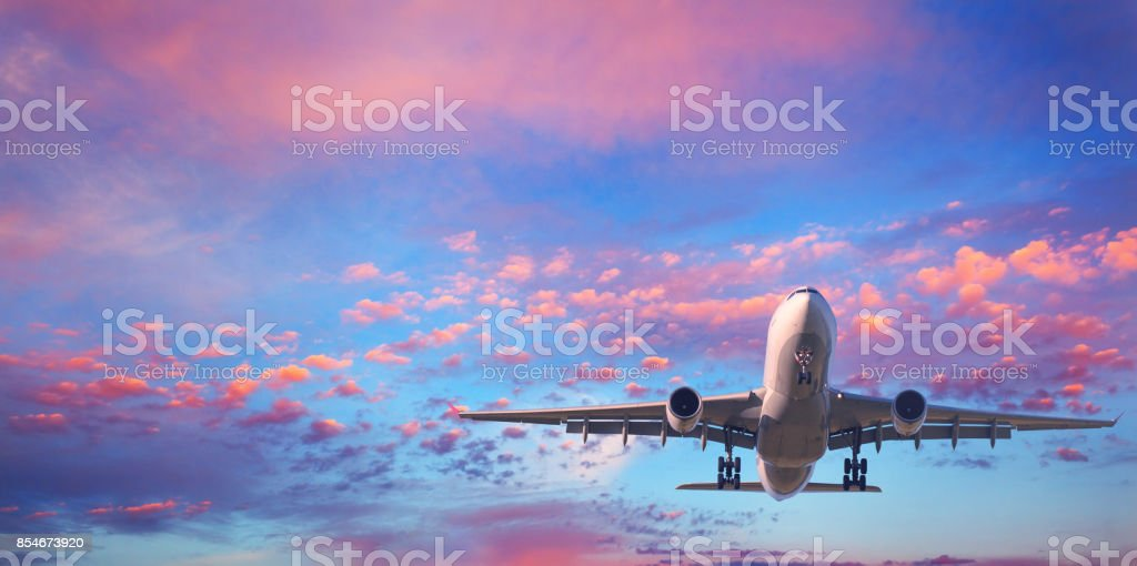 Landing airplane. Landscape with white passenger airplane is flying in the blue sky with pink clouds at sunset. Travel background. Passenger airliner. Business trip. Commercial aircraft. Private jet stock photo