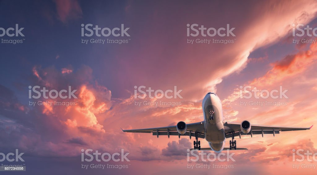 Landing airplane. Landscape with white passenger airplane is flying in the red sky with colorful clouds at sunset. Travel background. Passenger airliner. Business trip. Commercial aircraft.Private jet stock photo