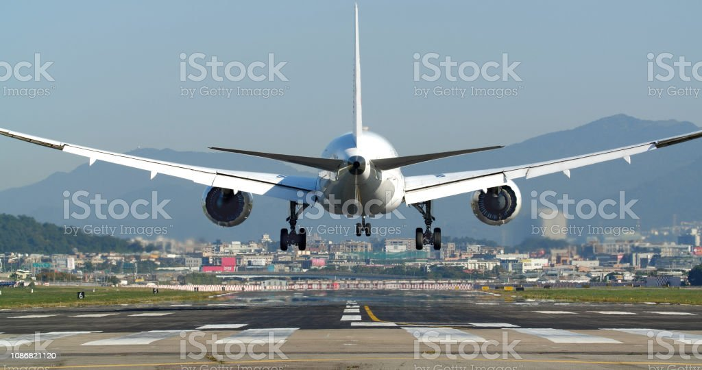The plane landing at the airport runwayThe plane landing at the...