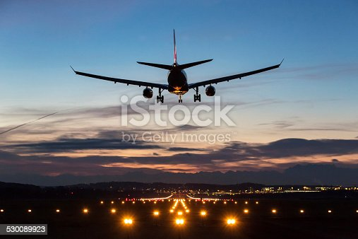Photo of an airplane just before landing in the early morning. Runway lights can be seen in the foreground.