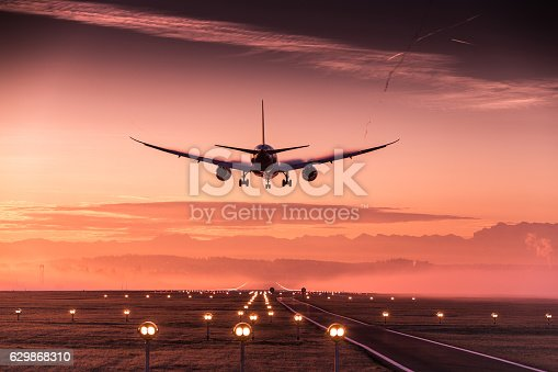 Airplane approaching the runway in the early morning. Runway lights can be seen in the foreground.