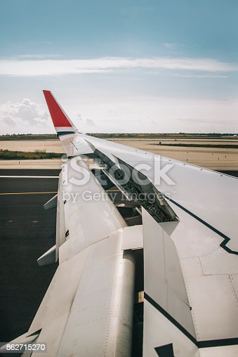 Detail of an airplane wing while landing in an airport.