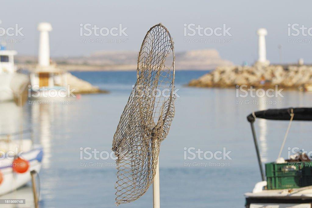 landing net and  fishing boat against blue mediterranean ocean royalty-free stock photo