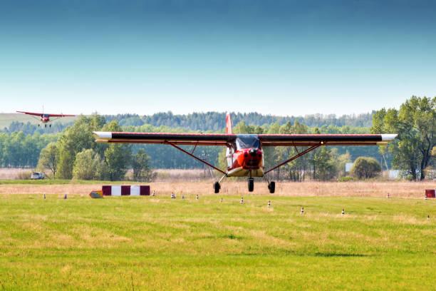 Landung von zwei roten Privatflugzeugen nacheinander auf einem kleinen Flugplatz – Foto