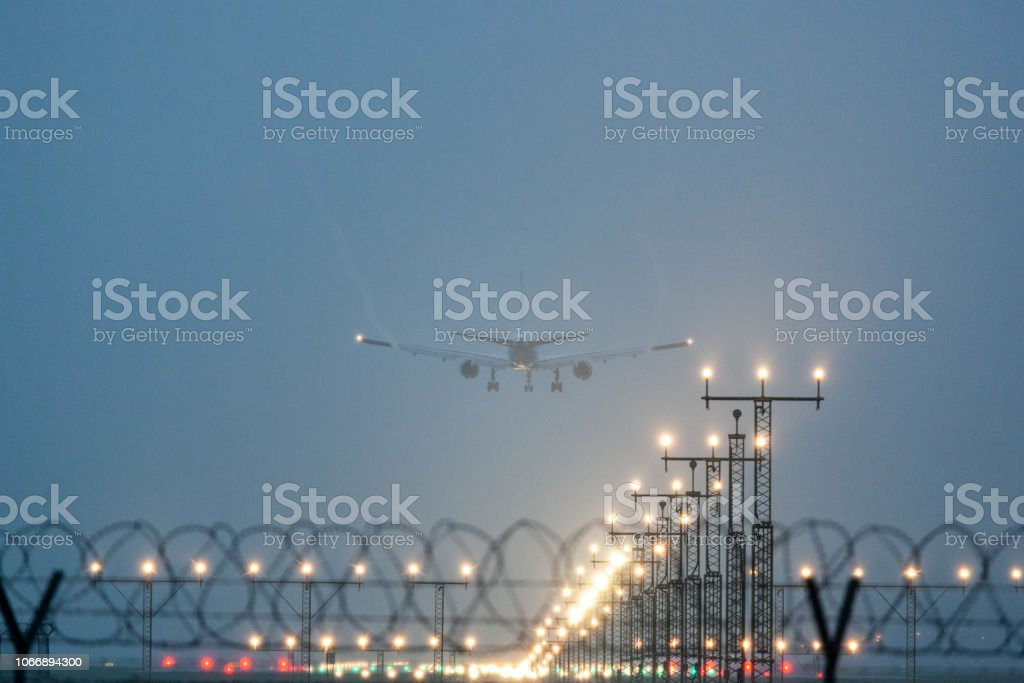 a commercial plane landing in a foggy and rainy day.