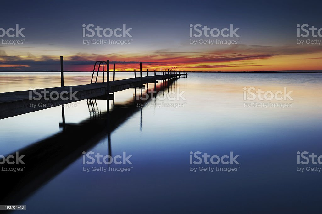Landing stage by the sea at sunset stock photo