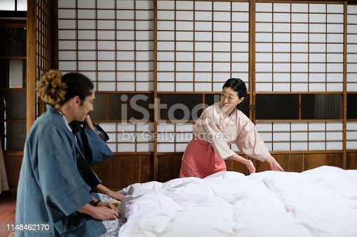 Land lady of ryokan (Japanese inn) explaining how to use futon