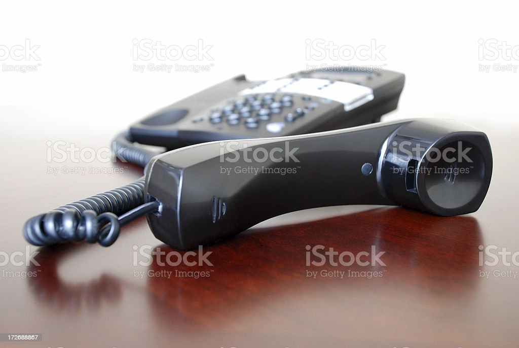 Landline Telephone Receiver off the Hook on a Brown Desk - Royalty-free Black Color Stock Photo