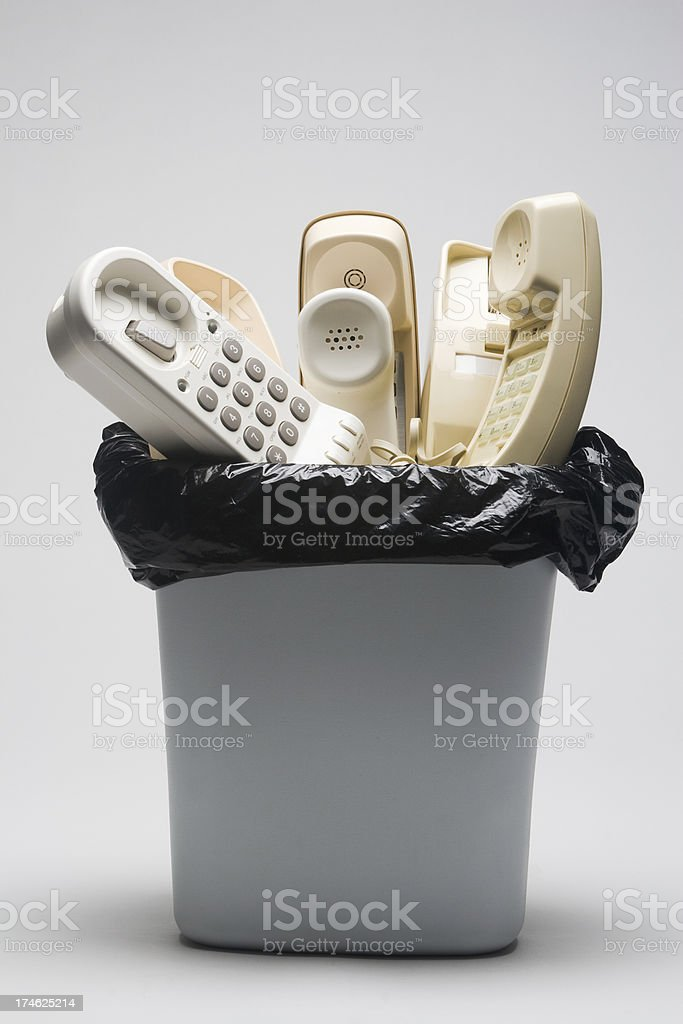 Landline telephones in a waste basket royalty-free stock photo