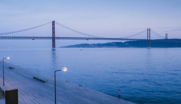 landmark 25 of april bridge on tagus river with cristo rei in background, lisbon, portugal - cristo rei lisboa imagens e fotografias de stock