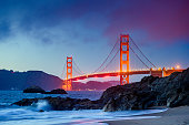 This is a photograph of the iconic Golden Gate Bridge from Baker's Beach in San Francisco at dusk.