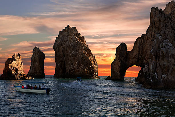 """Land's End & Arch at Sunset """"Land's End & the famous arch at sunset with boating (unrecognizable) tourists.  Cabo San Lucas, Baja, Mexico.See all Land's End:"""" natural arch stock pictures, royalty-free photos & images"""